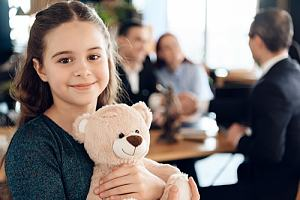 Child holding stuffed animal in legal office