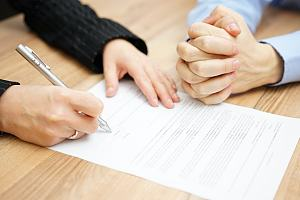 Couple signing postnuptial agreement