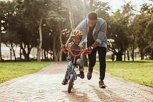 Father teaching son how to ride bike